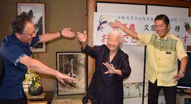 玉城デニー知事(左)や松本哲治浦添市長(右)とカチャーシーを踊る又吉芳子さん=16日、同市仲西の又吉さん宅