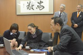 加山市長に現地の写真や動画を見せて説明する安藤さん(左)と高坂さん(左から2人目)=相模原市役所