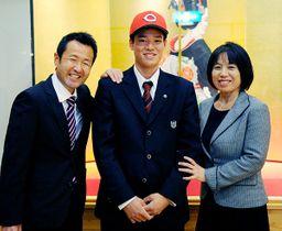 広島と仮契約し、父浩文さん(右)と母智子さんに挟まれてほほ笑む韮沢雄也=18日、加須市のサトエ記念21世紀美術館