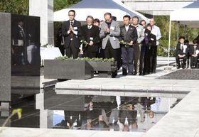 東京都の硫黄島戦没者慰霊式で、「鎮魂の丘」慰霊碑に献花をする遺族ら=18日午後、東京都小笠原村の硫黄島(代表撮影)