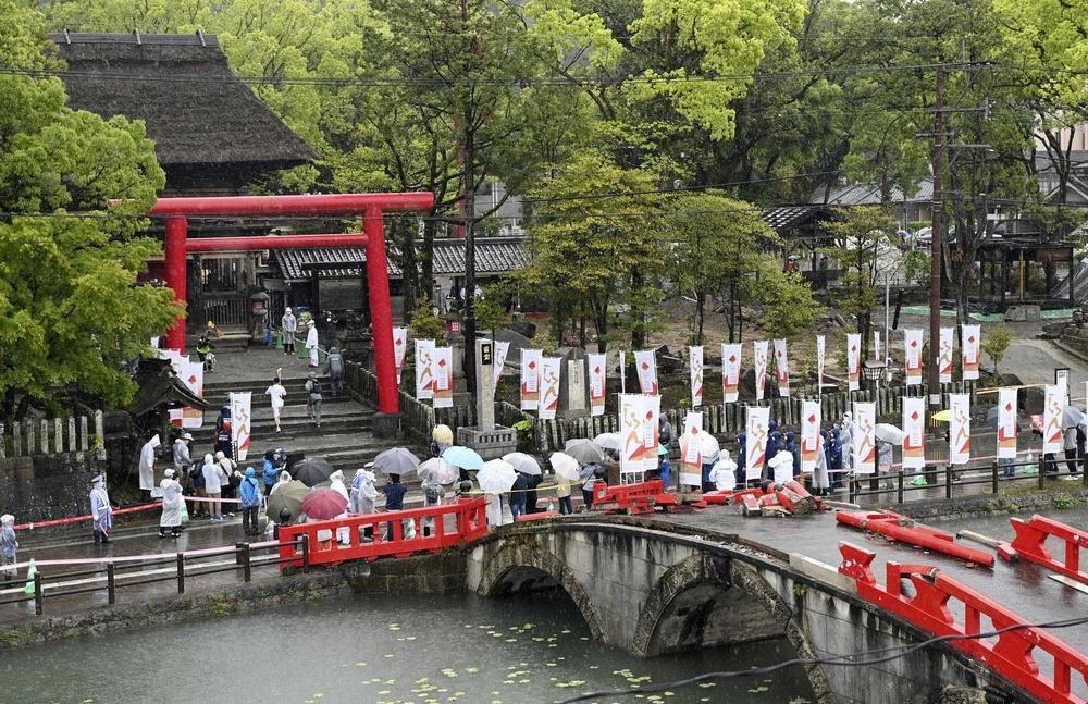 昨年7月に豪雨被害を受けた青井阿蘇神社を走る聖火ランナー。橋の欄干は壊れたまま=5日午前、熊本県人吉市