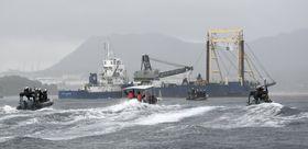 沖縄県名護市の辺野古沿岸部で、海保や反対派の船に囲まれ「K9護岸」に向かう砕石を積んだ台船=14日午前