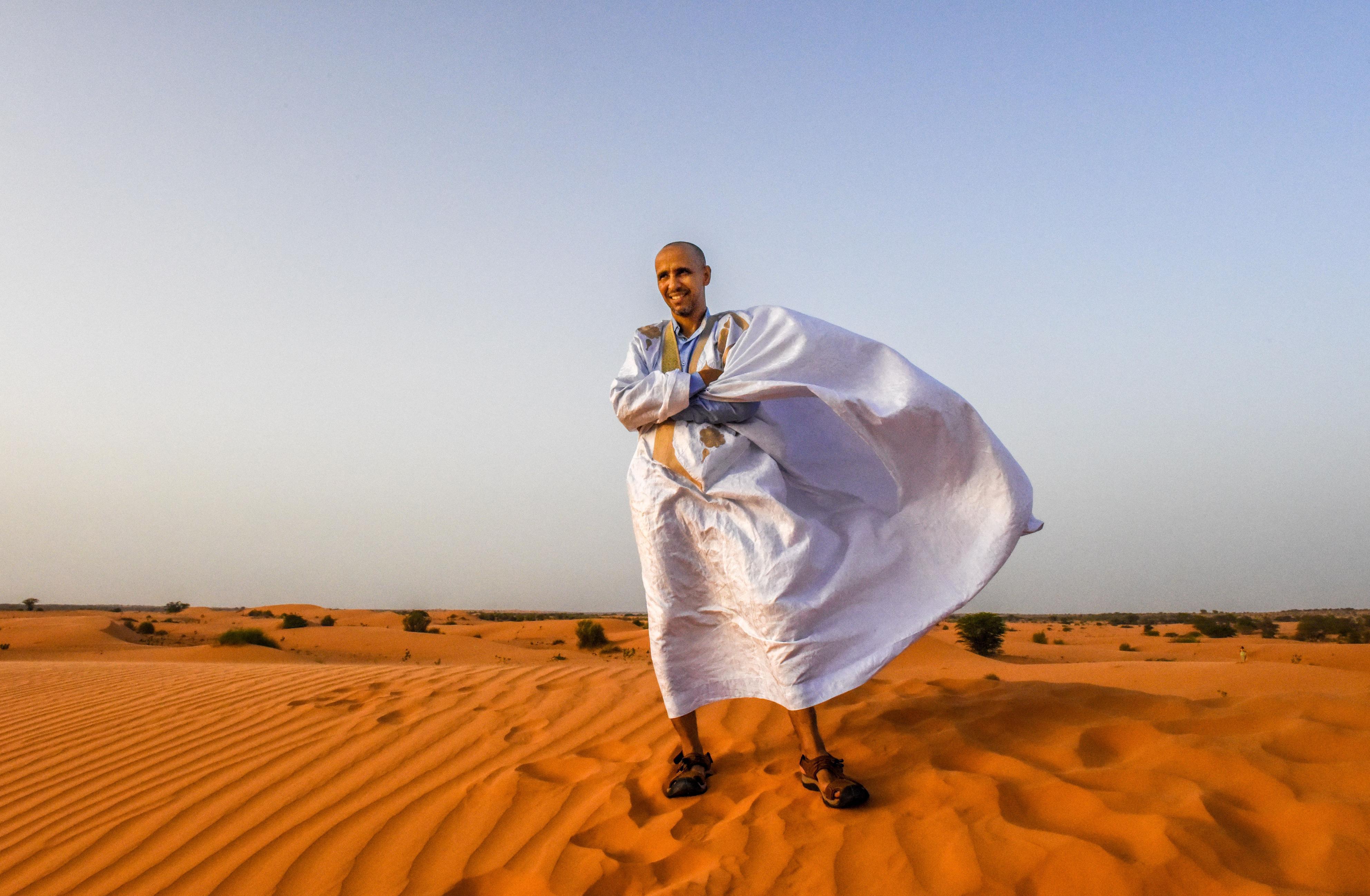 モーリタニアの首都ヌアクショット郊外の砂漠に立つモハメドゥ・スラヒ。強い風で民族衣装がはためき、夕日が砂地を赤く染める。足跡は翌朝までには消えるという。ラクダと砂漠はモハメドゥの子ども時代の思い出でもある(撮影・中野智明、共同)