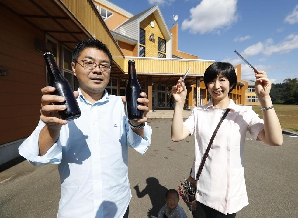 キイチゴビールを開発した鈴木矩彦(左)と美容師の畠山智美。2人とも起業して「馬場目ベース」(後方)に入居している=秋田県五城目町(撮影・浅川広則)\
