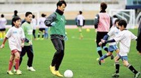 約100人の鹿児島市内の児童を対象にしたサッカー教室で指導する磐田の山田(中央)=鹿児島市の白波スタジアム