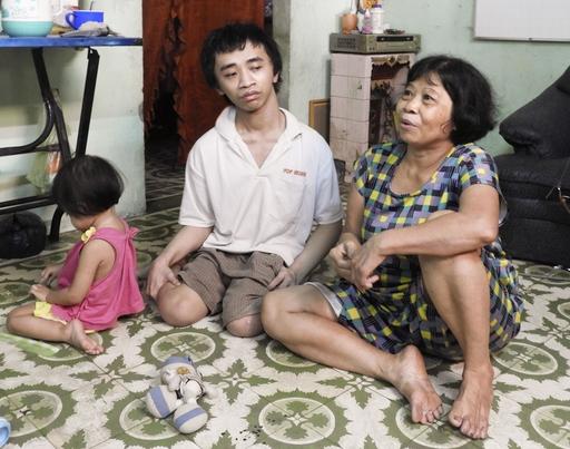 枯れ葉剤の影響で、生まれた時から両脚が動かせないホー・クアン・タイ。日中は幼いめい(左)の面倒を見て過ごすことが多い。母ブー・ティ・キム・リー(右)は10歳の頃、米軍機が枯れ葉剤をまくのを目撃した=19年9月、ベトナム・ビエンホア(撮影・石川文洋、共同)