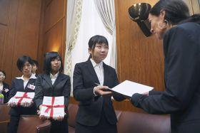 20日、国連軍縮会議の事務取りまとめを担うカスパーセン部長(右端)に反核署名の目録を手渡す松田小春さん(右から2人目)ら高校生平和大使=ジュネーブ(共同)