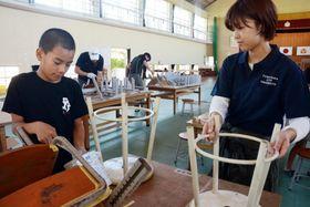 再利用するいすに色を塗る児童と大学生=さつま町の旧白男川小学校
