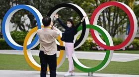五輪マークのモニュメントと記念撮影する女性=4月22日、東京都新宿区