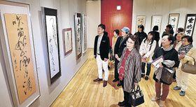 県書美術連盟の出品作を楽しむ来場者=北國新聞交流ホール