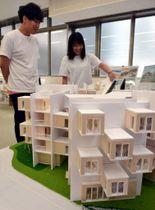 ユニークな学生寮の模型を紹介する北原さん(左)と河田さん
