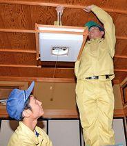 電灯の取り外し作業を行う、松江工業高校3年の立原柚人さん(左)と、井山颯一郎さん
