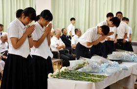 犠牲者を悼んで花を手向け、手を合わせる参列者