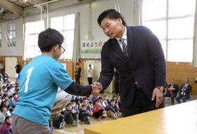 地元の結小学校で、児童の代表と握手する稲垣啓太選手=20日午前、新潟市秋葉区