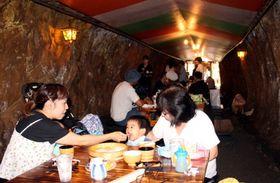 旧海軍が掘った洞窟の中でそうめんを食べる家族連れ=佐世保市、九十九島シーサイドテラスホテル&スパ花みずき