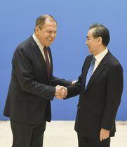 上海協力機構の外相会議を前に握手するロシアのラブロフ外相(左)と中国の王毅国務委員兼外相=24日、北京(共同)