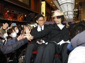 レッドカーペットに向かう人力車からファンに応える斉藤工さん(右)=19日午後、道後湯之町