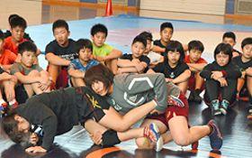 渡利璃穏選手(中央)と小西桂選手(左)のタックルの実演に見入る児童たち