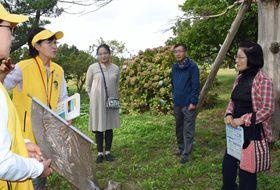 田小屋野貝塚で見つかった人骨について、ボランティアガイド(左側)の説明を聞くツアー参加者