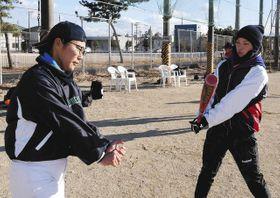 バッティングの見本を見せる浅野桜子さん(右)=浜松市南区で