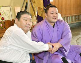 初優勝した大相撲夏場所の千秋楽から一夜明けた記者会見で、師匠の高砂親方(左)と握手する朝乃山=27日午前、東京都墨田区の高砂部屋