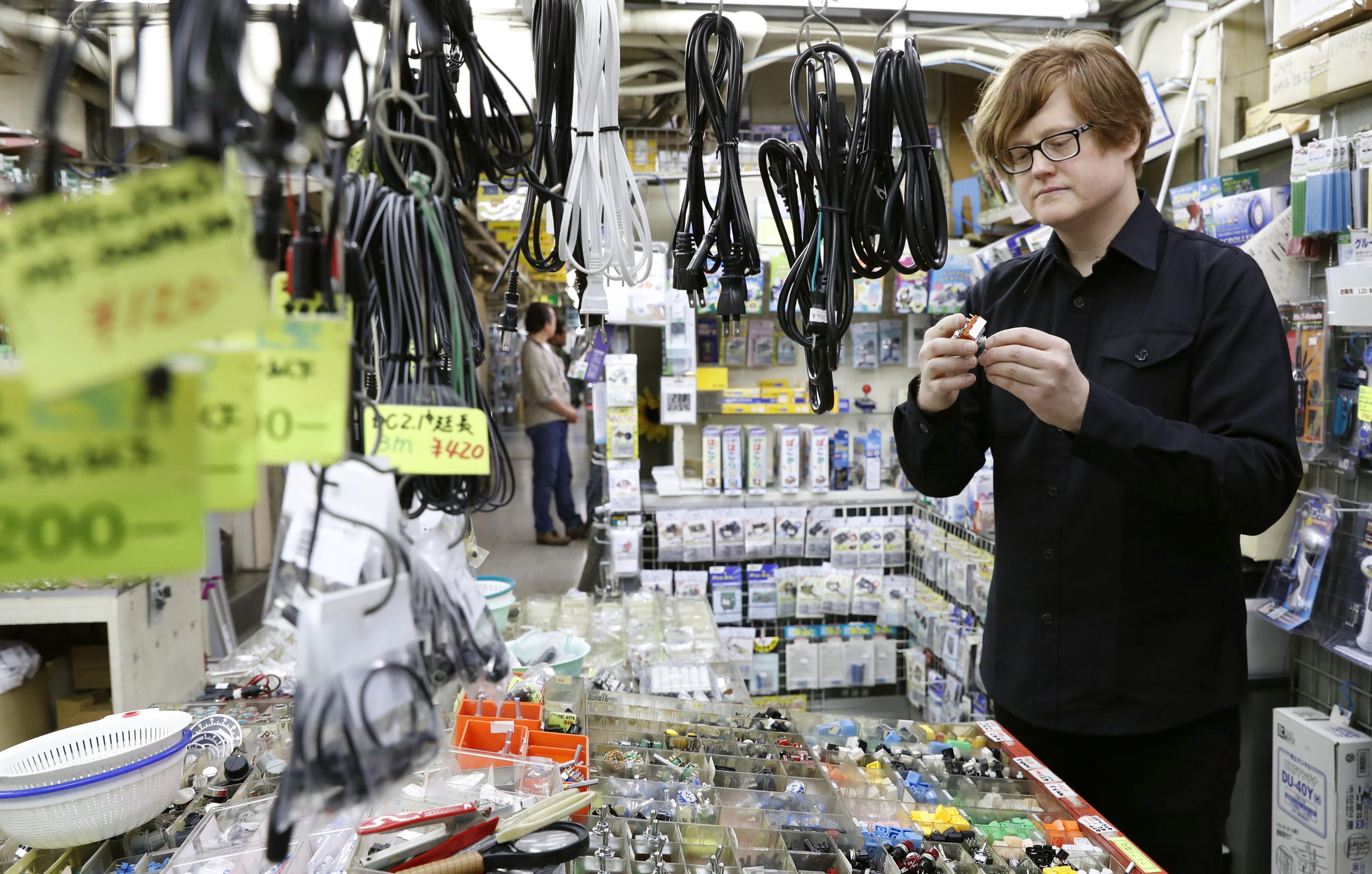 電子機器専門店で部品を手に取る米国のIT技術者。観光の途中に立ち寄ったといい「すばらしい」を繰り返した=東京・秋葉原
