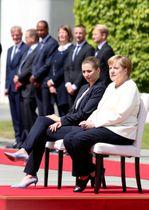 式典での国歌演奏中、着席するドイツのメルケル首相(手前右)とデンマークのフレデリクセン首相=11日、ベルリン(ゲッティ=共同)