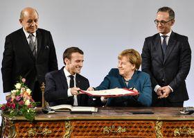 新条約「アーヘン条約」の調印式で、署名を交わすドイツのメルケル首相(前列右)とフランスのマクロン大統領(同左)=22日、ドイツ西部アーヘン(AP=共同)