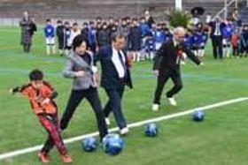 始球式でボールを蹴る子どもや地元のスポーツ関係者ら=10日、宇部市