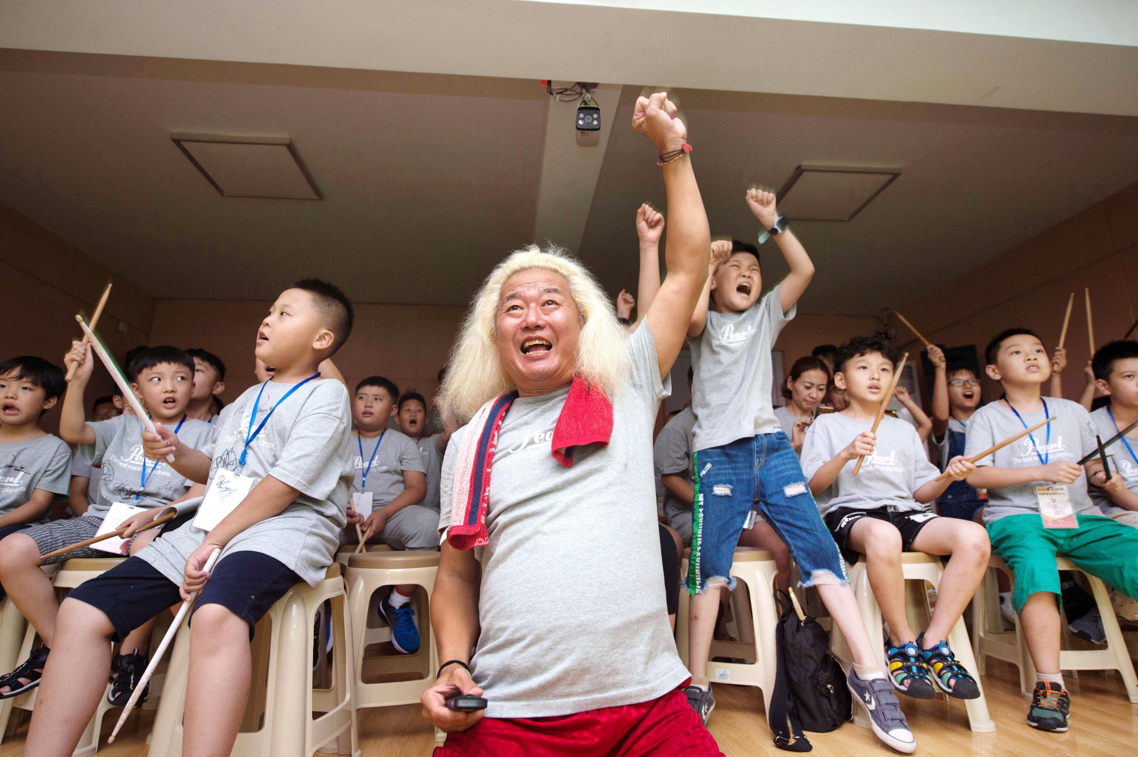 ドラムのサマースクールで、仲間の演奏するロックのリズムに合わせて熱狂する生徒たちとファンキー末吉。子どもたちは音楽を通じ、初めて出会った日本人講師たちとすぐに打ち解けた=中国山東省臨沂市(撮影・池上まどか、共同)