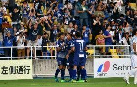 後半9分、ゴールを決め祝福される福岡の駒野(手前中央)。サポーターも喜ぶ