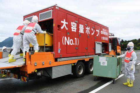 大飯原発と高浜原発の同時事故を想定した訓練で、大容量ポンプとホースを接続する関西電力社員=9月、福井県おおい町