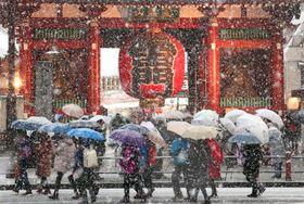 雪の降る中、東京・浅草寺の雷門前を歩く観光客ら=22日午後