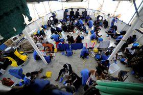 マルタとイタリア領リノーザ島の間の地中海に浮かぶ船上の難民たち=14日(ロイター=共同)