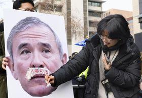 13日、ソウルの米大使館周辺でハリス駐韓米大使の写真にいたずらをする集会参加者(共同)