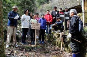 完成した案内看板を手に住民グループのメンバー(両端)と話す児童たち