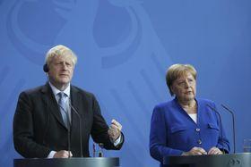 21日、ベルリンで初会談後に記者会見するジョンソン英首相(左)とドイツのメルケル首相(ゲッティ=共同)