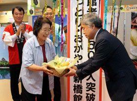 250万人目の入館者となり、記念品を受け取る佐久間さん(手前左)