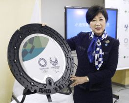 東京都が設置する2020年東京五輪・パラリンピックのエンブレムをデザインしたマンホールのふたを紹介する小池百合子知事=13日午後、東京都庁