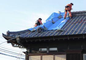 台風15号で被害を受けた屋根の修復作業をする消防隊員=19日午後、千葉県八街市