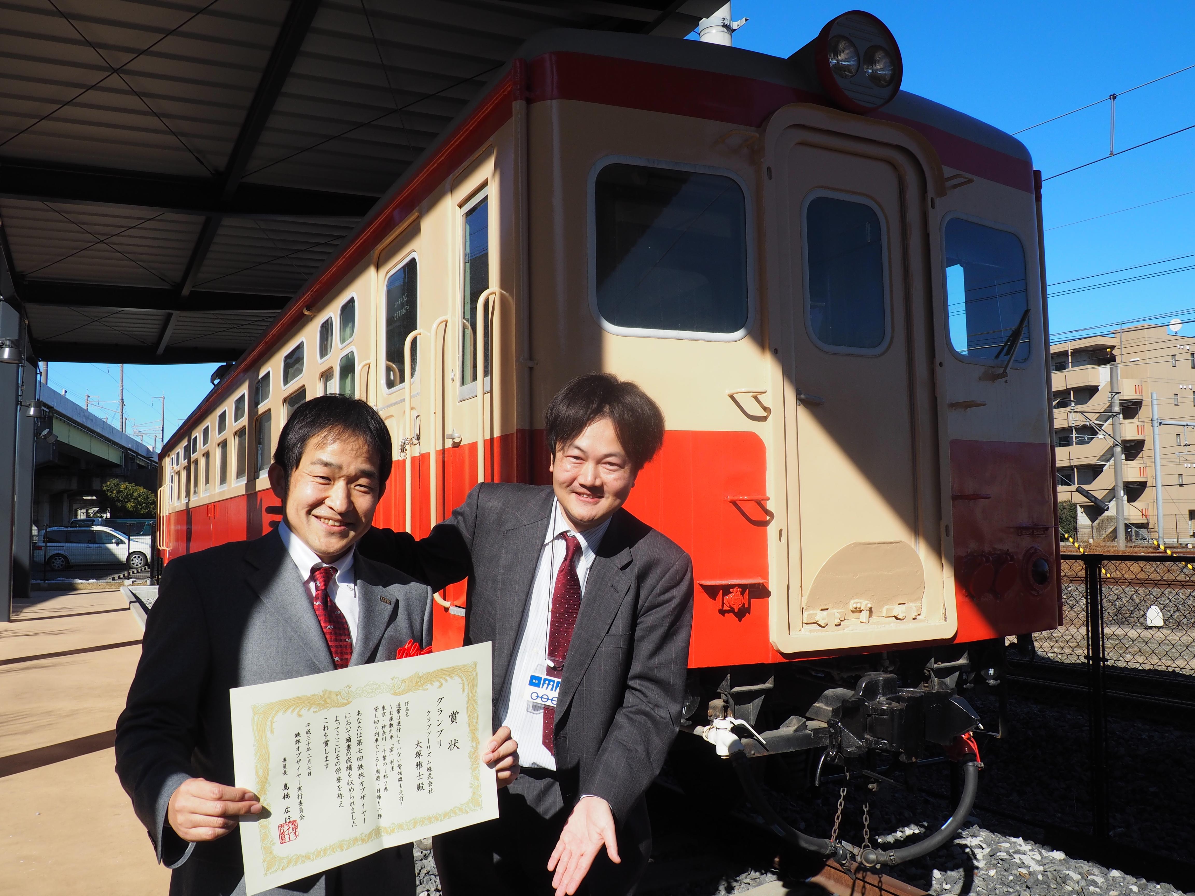 2017年度の「鉄旅オブザイヤー」授賞式で、旅行会社部門のグラ ンプリを受賞したクラブツーリズムの大塚雅士さん(左)と筆者=2月7日、さいたま市の鉄道博物館