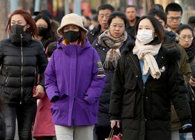 21日、北京中心部でマスクをする市民(UPI=共同)