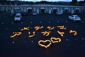愛島東部仮設住宅前に浮かび上がる「メデシマ アリガトウ」の文字=15日夕、宮城県名取市