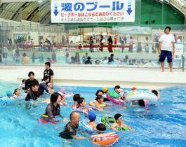 プールで人工の波を楽しむ家族連れたち