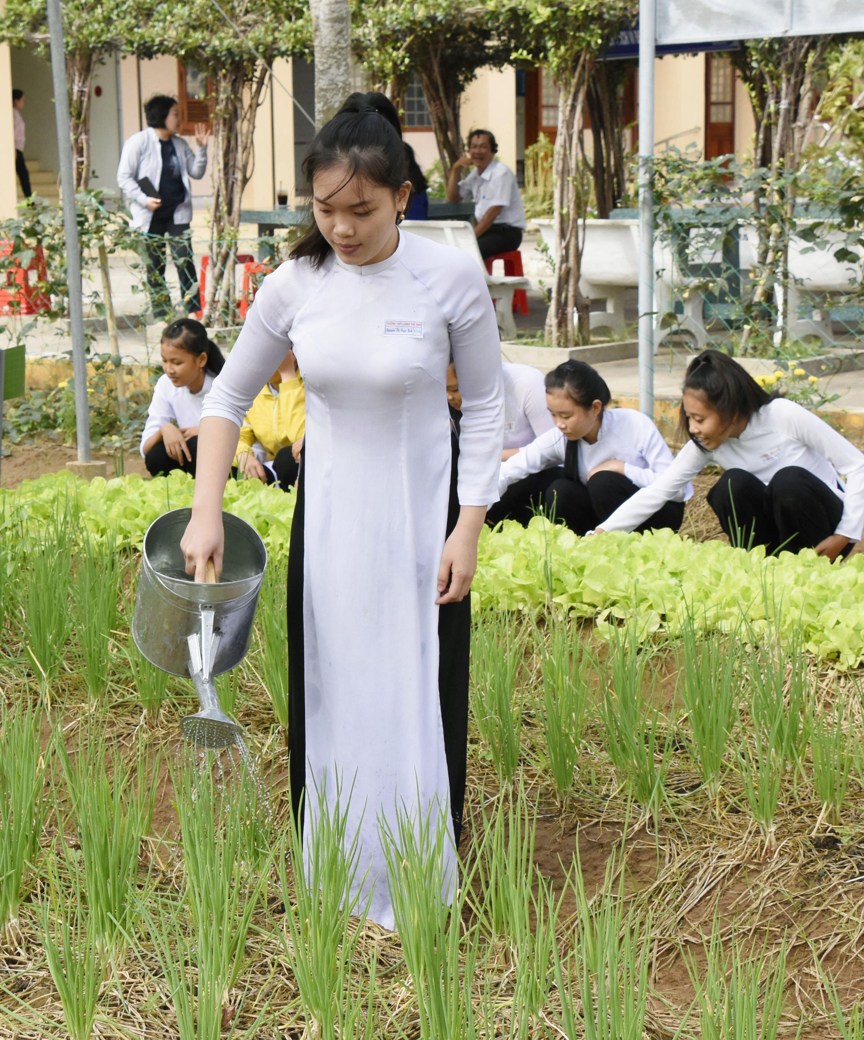 校庭に作られた菜園で、水やりをするルオンテービン高校の生徒。収穫した野菜は地元の市場で売られ、食卓に並ぶ
