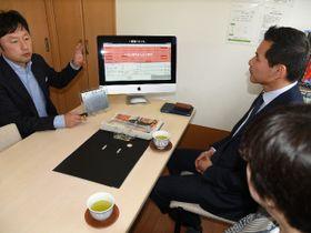 業務の効率化を目指し開発した「ラクウェア」の概要を尾関健治市長らに説明する三鴨正貴社長(左)=関市小屋名、ラクアデイサービス関