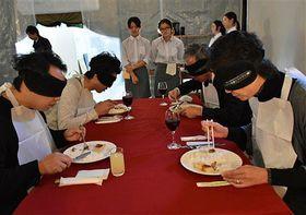 アイマスクで視覚がさえぎられる「暗闇レストラン」で、料理を楽しむ招待客