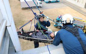 担架に乗り、要救助者役を体験する学生=高松市多肥下町、県警機動隊庁舎