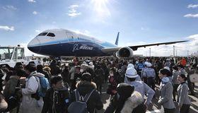 けん引車に引かれて登場したボーイング787の初号機と、集まった大勢の航空ファンら=17日午後、中部空港