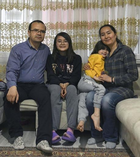 亡命先のトルコ・イスタンブールの自宅で、家族と撮影に応じるアブドゥエリ・アユプ(左端)。無国籍のままでの不安定な生活が続く=3月(共同)